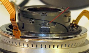The plastic collar around the screw keeps the lens tracking properly in the helicoid groove.